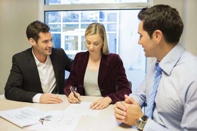 kobieta podopisuje umowę w towarzystwie dwóch mężczyzn