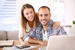 uśmiechnięta kobieta i meżczyzna przy biurku