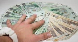 ręka sięga po banknoty