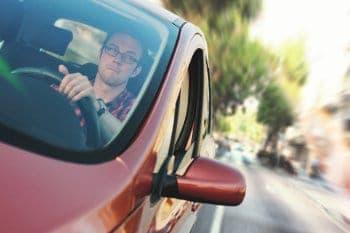 młody mężczyzna prowadzi samochód