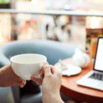 Kobieta siedzi z kawą przy laptopie