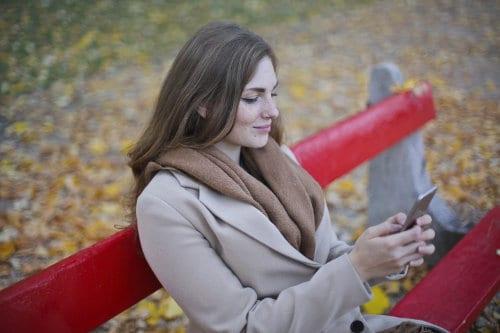 Kobieta siedzi na ławce i sprawdza telefon komórkowy