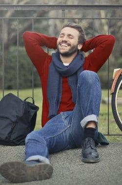 Młody uśmiechnięty mężczyzna siedzi na ziemi i opiera się o barierkę