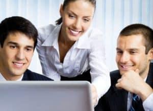 uśmiechnięci młodzi ludzie ubrani biurowo w pracy