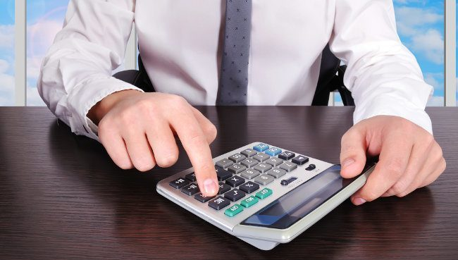 mężczyzna dokonuje obliczeń na kalkulatorze