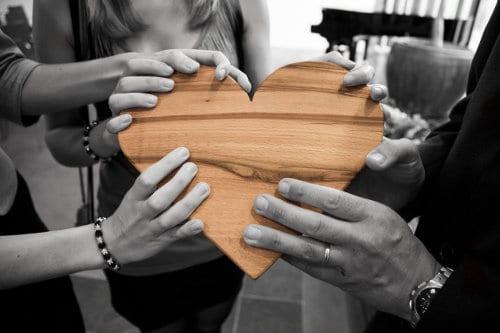Ludzie trzymają serce z drewna