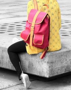 studentka siedzi na murku z plecakiem