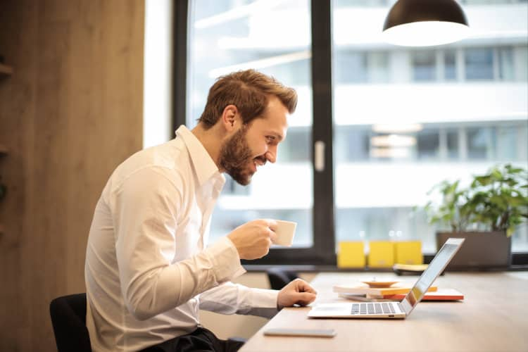 Mężczyzna z kubkiem kawy siedzi przy laptopie